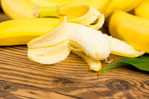 Photo of peeled bananas on wooden board